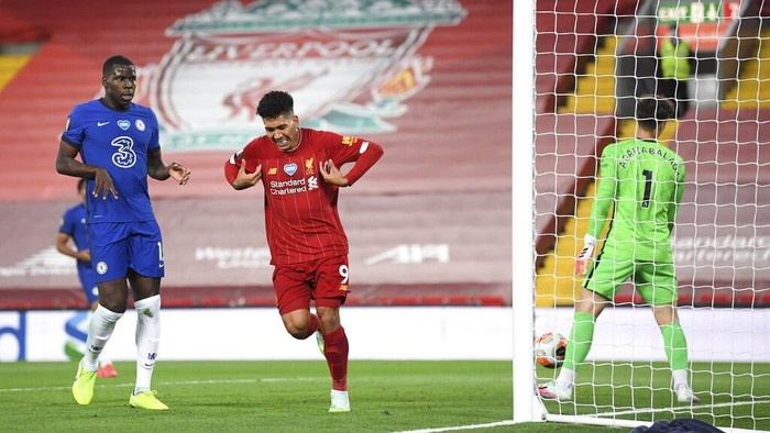 Liverpools Roberto Firmino, center, celebrates scoring his sides fourth goal during the English Premier League soccer match between Liverpool and Chelsea at Anfield stadium in Liverpool, England, Wednesday, July 22, 2020. (Laurence Griffiths, Pool via AP)