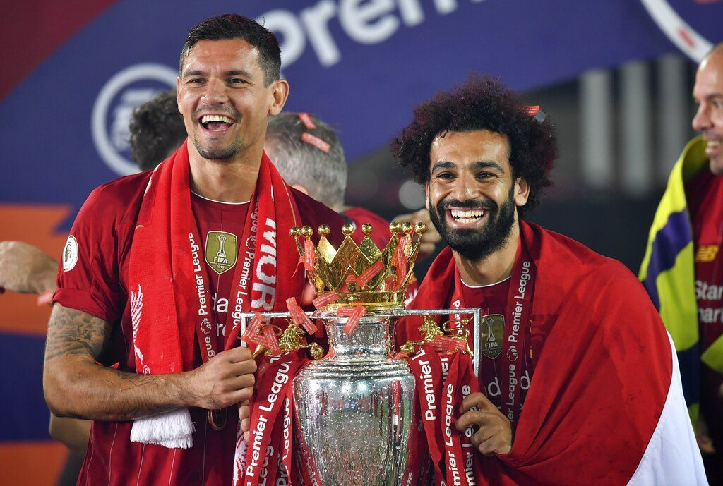 Liverpool's Dejan Lovren and Liverpool's Mohamed Salah celebrate with the English Premier League trophy aloft after it was presented following the Premier League soccer match between Liverpool and Chelsea at Anfield stadium in Liverpool, England, Wednesday, July 22, 2020. (Paul Ellis, Pool via AP)