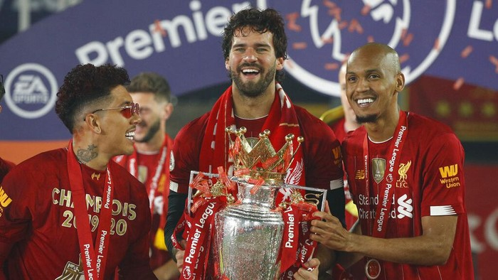Liverpools Roberto Firmino, left, Liverpools goalkeeper Alisson, center, and Liverpools Fabinho, celebrate with the English Premier League trophy following its presentation to the team for winning the EPL 2019-2020 season after the soccer match between Liverpool and Chelsea at Anfield Stadium in Liverpool, England, Wednesday, July 22, 2020. Liverpool won the match 5-3. (Phil Noble/Pool via AP)