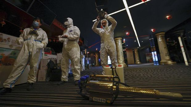 Volunteers with the Blue Sky Rescue team prepare to disinfect of a cineplex before it reopens for business in Beijing Friday, July 24, 2020. Theaters in China, the world's second largest movie market, this week reopened from the coronavirus shut down with theaters limited to 30% capacity. (AP Photo/Ng Han Guan)