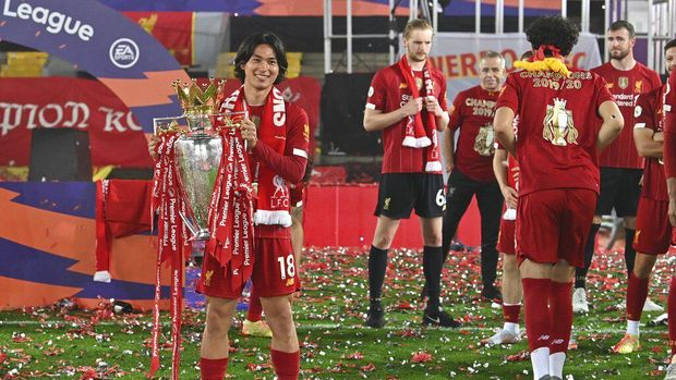 Liverpool's Takumi Minamino holds the English Premier League trophy aloft after it was presented following the Premier League soccer match between Liverpool and Chelsea at Anfield stadium in Liverpool, England, Wednesday, July 22, 2020. (Paul Ellis, Pool via AP)