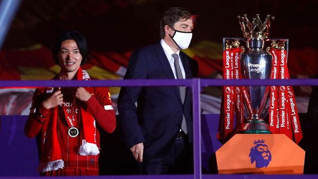 LIVERPOOL, ENGLAND - JULY 22: Takumi Minamino of Liverpool receives a Premier League Winner's medal following the Premier League match between Liverpool FC and Chelsea FC at Anfield on July 22, 2020 in Liverpool, England. Football Stadiums around Europe remain empty due to the Coronavirus Pandemic as Government social distancing laws prohibit fans inside venues resulting in all fixtures being played behind closed doors. (Photo by Phil Noble/Pool via Getty Images)