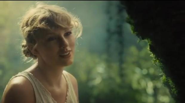 Taylor Swift memilih menata rambutnya dengan kepang dua, lalu mencepolnya sehingga menambah kesan folk.