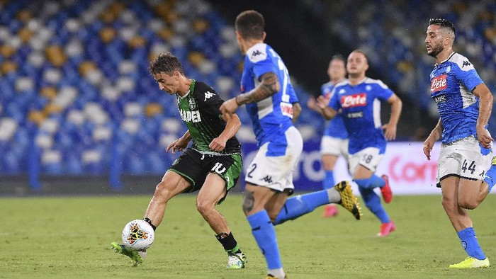 Sassuolos Filip Djuricic, left, vies for the ball during the Italian Serie A soccer match between Napoli and Sassuolo, at the San Paolo stadium in Naples, Italy, Saturday, July 25, 2020. (Cafaro/LaPresse via AP)