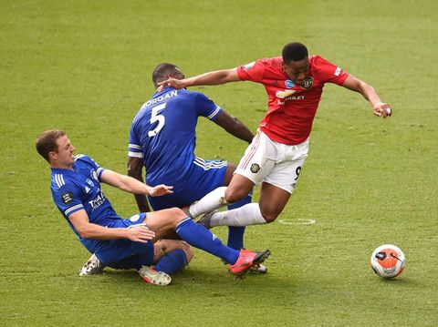LEICESTER, ENGLAND - JULY 26: Anthony Martial of Manchester United is tackled by Wes Morgan and Jonny Evans both of Leicester City leading to a penalty during the Premier League match between Leicester City and Manchester United at The King Power Stadium on July 26, 2020 in Leicester, England.Football Stadiums around Europe remain empty due to the Coronavirus Pandemic as Government social distancing laws prohibit fans inside venues resulting in all fixtures being played behind closed doors. (Photo by Oli Scarff/Pool via Getty Images)