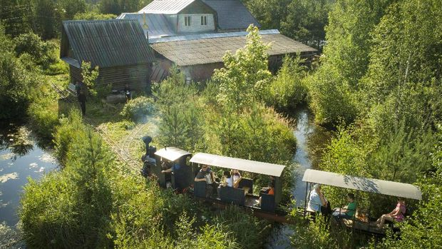 A miniature steam train runs across a bridge on Pavel Chilin's miniature personal narrow-gauge railway twisting through the grounds of his home in Ulyanovka village outside St. Petersburg, Russia Sunday, July 19, 2020. It took Chilin more than 10 years to build a 350-meter-long mini-railway twisting through the grounds of his cottage home about 50 kilometers (some 30 miles) outside St. Petersburg, complete with various branches, dead ends, circuit loops, and even three bridges.(AP Photo/Dmitri Lovetsky)
