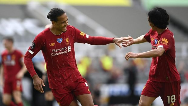Liverpool's Virgil van Dijk, left, celebrates with Takumi Minamino after his side's first goal during the English Premier League soccer match between Newcastle and Liverpool at St. James' Park in Newcastle, England, Sunday, July 26, 2020. (Laurence Griffiths, Pool via AP)