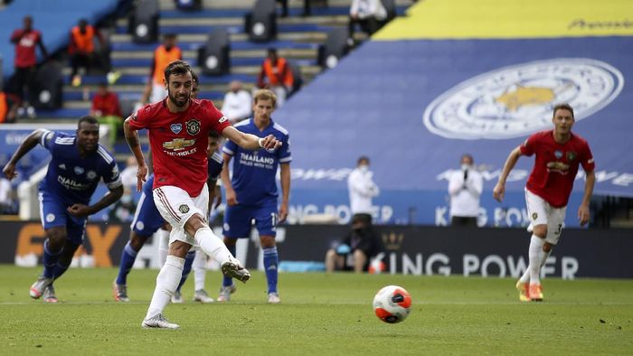 Manchester Uniteds Bruno Fernandes, front, scores his sides opening goal from the penalty spot during the English Premier League soccer match between Leicester City and Manchester United at the King Power Stadium, in Leicester, England, Sunday, July 26, 2020. (Carl Recine/Pool via AP)