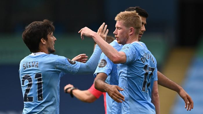 MANCHESTER, ENGLAND - JULY 26: Kevin De Bruyne of Manchester City and teammate David Silva celebrate after scoring his sides second goal during the Premier League match between Manchester City and Norwich City at Etihad Stadium on July 26, 2020 in Manchester, England.Football Stadiums around Europe remain empty due to the Coronavirus Pandemic as Government social distancing laws prohibit fans inside venues resulting in all fixtures being played behind closed doors. (Photo by Shaun Botterill/Getty Images)