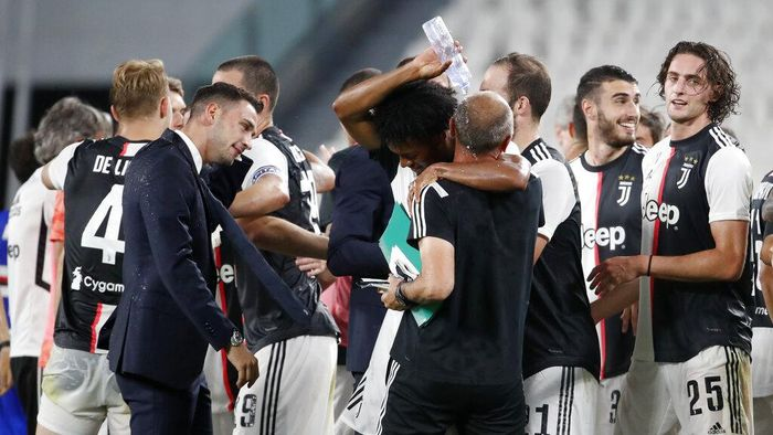Juventus players celebrate at the end of Serie A soccer match between Juventus and Sampdoria at the Allianz stadium, in Turin, Italy, Sunday, July 26, 2020. Juventus clinched a record-extending ninth successive Serie A title after it defeated Sampdoria 2-0. (AP Photo/Antonio Calanni)