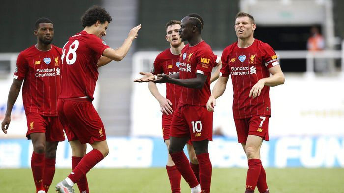 Liverpools Sadio Mane, center, celebrates with teammates after scoring his sides third goal during the English Premier League soccer match between Newcastle and Liverpool at St. James Park in Newcastle, England, Sunday, July 26, 2020. (Owen Humphreys, Pool via AP)