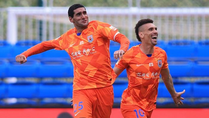 Marouane Fellaini (L) of Shandong Luneng celebrates with teammate Moises after Fellaini scored against Dalian Pro during their Chinese Super League (CSL) football match in Dalian in Chinas northeastern Liaoning province on July 26, 2020. - Fellaini, who spent three weeks in hospital with the COVID-19 coronavirus, scored a hat-trick of headers in less than 10 minutes to give Shandong Luneng a 3-2 victory over Rafa Benitezs Dalian Pro. (Photo by STR / AFP) / China OUT