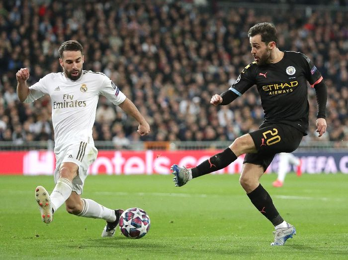 MADRID, SPAIN - FEBRUARY 26: Bernardo Silva of Manchester City shoots as Daniel Carvajal of Real Madrid attempts to block during the UEFA Champions League round of 16 first leg match between Real Madrid and Manchester City at Bernabeu on February 26, 2020 in Madrid, Spain. (Photo by Gonzalo Arroyo Moreno/Getty Images)