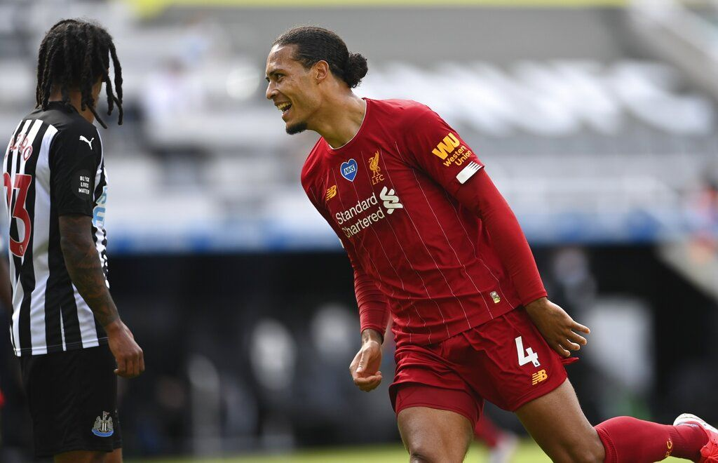 Liverpool's Virgil van Dijk celebrates after scoring his side's first goal during the English Premier League soccer match between Newcastle and Liverpool at St. James' Park in Newcastle, England, Sunday, July 26, 2020. (Laurence Griffiths, Pool via AP)