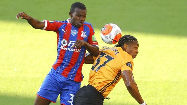 Crystal Palace's Joel Ward, left, and Wolverhampton Wanderers' Adama Traore battle for the ball during the English Premier League soccer match between Wolverhampton Wanderers and Crystal Palace at Molineux Stadium in Wolverhampton, England, Monday, July 20, 2020. (AP Photo/Richard Heathcote,Pool)