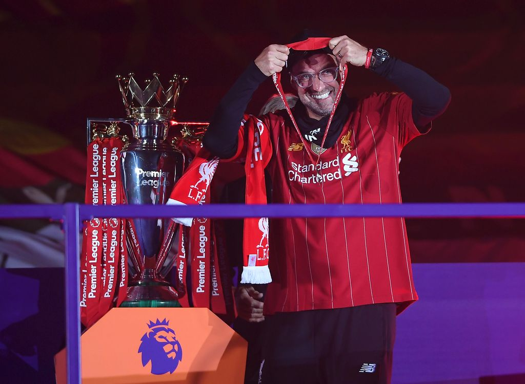 LIVERPOOL, ENGLAND - JULY 22: Jurgen Klopp, Manger of Liverpool puts on his winners medal during the presentation ceremony of  the Premier League match between Liverpool FC and Chelsea FC at Anfield on July 22, 2020 in Liverpool, England. Football Stadiums around Europe remain empty due to the Coronavirus Pandemic as Government social distancing laws prohibit fans inside venues resulting in games being played behind closed doors. (Photo by Laurence Griffiths/Getty Images)