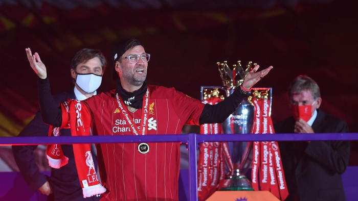 LIVERPOOL, ENGLAND - JULY 22: Jurgen Klopp, Manger of Liverpool puts on his winners medal after being presented by Richard Masters, Chief Executive of the Premier League and Liverpool legend Sir Kenny Dalglish during the Presentation ceremony of  the Premier League match between Liverpool FC and Chelsea FC at Anfield on July 22, 2020 in Liverpool, England. Football Stadiums around Europe remain empty due to the Coronavirus Pandemic as Government social distancing laws prohibit fans inside venues resulting in games being played behind closed doors. (Photo by Laurence Griffiths/Getty Images)