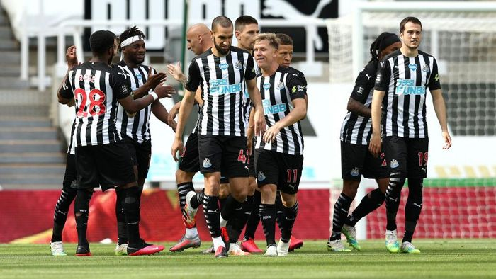 NEWCASTLE UPON TYNE, ENGLAND - JULY 26: Newcastle United players celebrate their teams first goal during the Premier League match between Newcastle United and Liverpool FC at St. James Park on July 26, 2020 in Newcastle upon Tyne, England. Football Stadiums around Europe remain empty due to the Coronavirus Pandemic as Government social distancing laws prohibit fans inside venues resulting in all fixtures being played behind closed doors. (Photo by Jan Kruger/Getty Images )