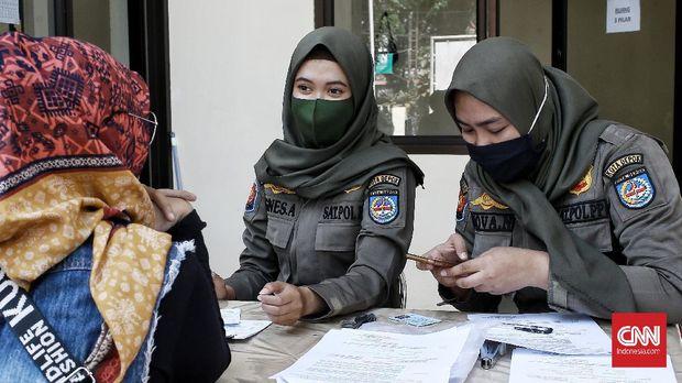 Petugas memberikan denda kepada warga yang tidak mengenakan masker di kawasan Jalan Sukmajaya, Depok, Jawa Barat, Senin (28/7/2020). Warga yang tidak mengenakan masker dikenai denda Rp 50 ribu.CNN Indonesia/Andry Novelino