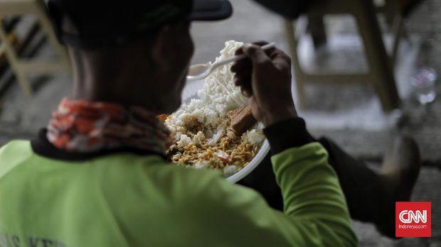 Warga makan dan minum gratis dengan tetap menjaga jarak di Jalan Basuki Rachmat, Jakarta Timur, Rabu, 29 Juli 2020. Makan gratis dimulai hari Senin hingga Jumat, pukul 12.00 sampai 14.00 WIB. Sebanyak 100-140 porsi makan siang gratis disediakan setiapharinya. Protokol kesehatan Covid-19 juga dilakukan selama makan gratis di tempat tersebut. (CNN Indonesia/ Adhi Wicaksono)