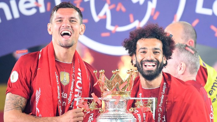 LIVERPOOL, ENGLAND - JULY 22: Dejan Lovren and Mohamed Salah of Liverpool celebrate with the Premier League Trophy after winning during the presentation ceremony of  the Premier League match between Liverpool FC and Chelsea FC at Anfield on July 22, 2020 in Liverpool, England. Football Stadiums around Europe remain empty due to the Coronavirus Pandemic as Government social distancing laws prohibit fans inside venues resulting in games being played behind closed doors. (Photo by Laurence Griffiths/Getty Images)