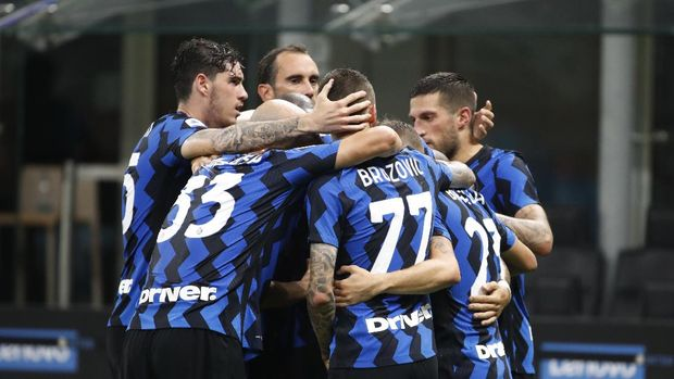 Inter Milan's Lautaro Martinez, obscured, celebrates with his teammates after scoring g against Napoli, during the Serie A soccer match between Inter Milan and Napoli at the San Siro Stadium, in Milan, Italy, Tuesday, July 28, 2020. (AP Photo/Antonio Calanni)