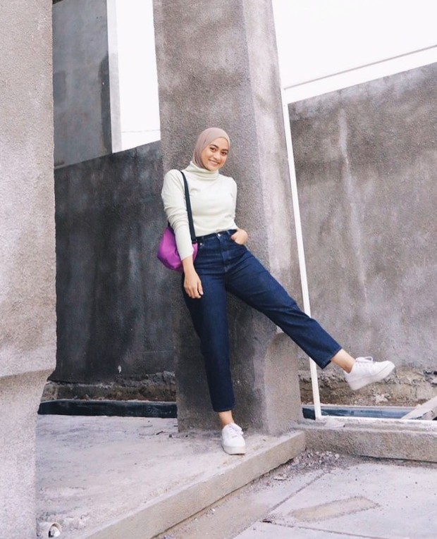 Untuk tampilan kasual, Ayudia memadukan hijab dengan atasan turtleneck light gray yang dimasukkan ke celana jeans highwaist berwarna dark blue.