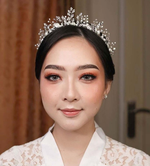 Asta Riri memilih menggunakan makeup flawless dengan nuansa oranye pada akad nikahnya.