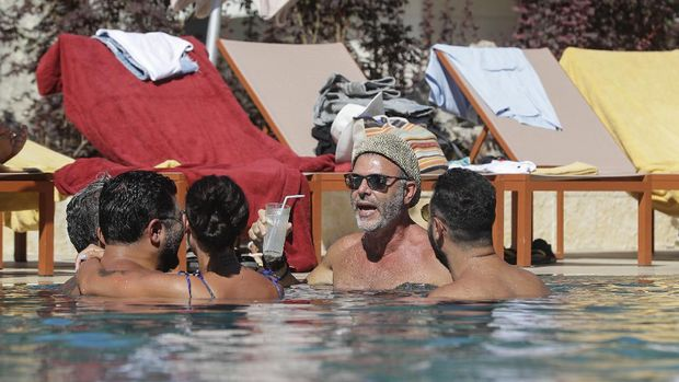 Lebanese people gather at a swimming pool in the upmarket Faqra Club in the Lebanese mountains north of Beirut on July 25, 2020. - Panama hats and designer sunglasses, champagne buckets and luxury cars: in the mountain resort town of Faqra, Lebanon's economic crisis is not immediately obvious. Digging into a crunchy salad at an exclusive country club in the Lebanese mountains, Zeina el-Khalil said she was glad to have escaped here for the summer. (Photo by JOSEPH EID / AFP)