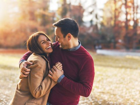 Couple in love hugging and enjoying at public park in autumn