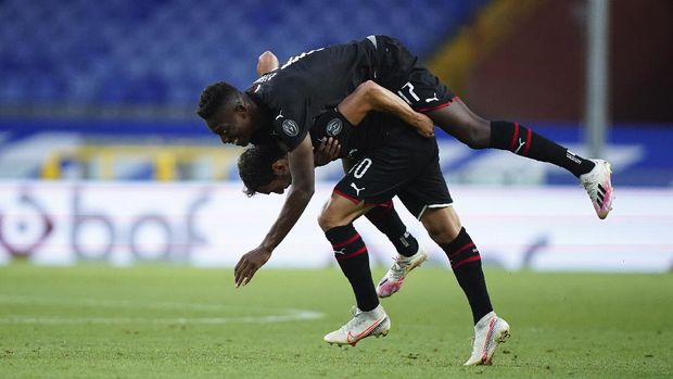 Milan's  Hakan Calhanoglu, bottom, celebrates with teammate Rafael Leao after scoring his side's second goal during the Italian Serie A match between Sampdoria and Milan at the Luigi Ferraris stadium in Genoa, Italy, Wednesday, July 29, 2020.  (Spada/LaPresse via AP)