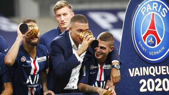 PSGs Kylian Mbappe, centre, who did not play due to an injury, celebrates with his teammates after the team won the French League Cup, following the soccer final match against Lyon at Stade de France stadium, in Saint Denis, north of Paris, Friday, July 31, 2020. (AP Photo/Francois Mori)