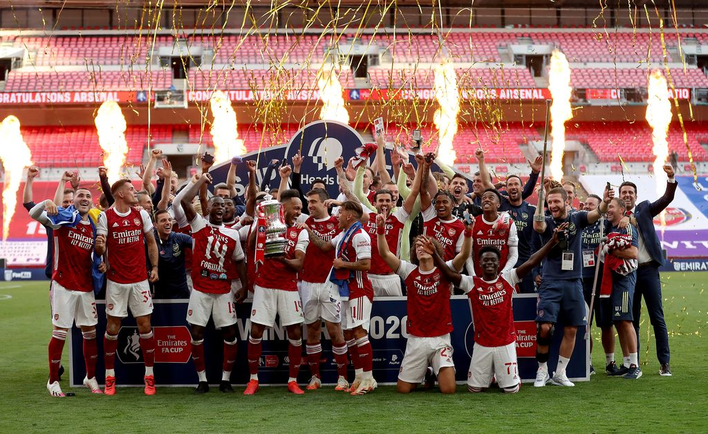 LONDON, ENGLAND - AUGUST 01: Pierre-Emerick Aubameyang of Arsenal lifts the FA Cup Trophy with his team mates after their victory in the Heads Up FA Cup Final match between Arsenal and Chelsea at Wembley Stadium on August 01, 2020 in London, England. Football Stadiums around Europe remain empty due to the Coronavirus Pandemic as Government social distancing laws prohibit fans inside venues resulting in all fixtures being played behind closed doors. (Photo by Catherine Ivill/Getty Images)