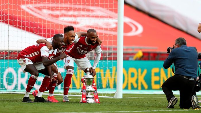 LONDON, ENGLAND - AUGUST 01: Nicolas Pepe of Arsenal , Pierre-Emerick Aubameyang of Arsenal  and Alexandre Lacazette of Arsenal pose for photographs with the FA Cup Trophy after their teams victory during the Heads Up FA Cup Final match between Arsenal and Chelsea at Wembley Stadium on August 01, 2020 in London, England. Football Stadiums around Europe remain empty due to the Coronavirus Pandemic as Government social distancing laws prohibit fans inside venues resulting in all fixtures being played behind closed doors. (Photo by Catherine Ivill/Getty Images)