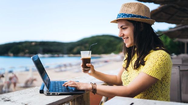 Young Caucasian beautiful woman using laptop and having a drink in beach café.