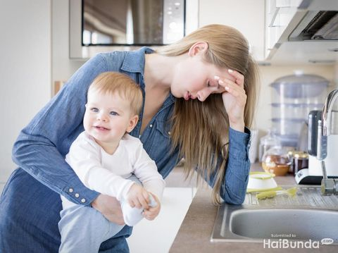 Tired concerned new mother rocking crying baby in kitchen. Portrait of young woman and cute little child in home interior. Motherhood concept