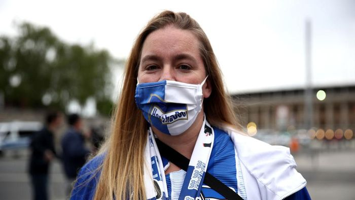 BERLIN, GERMANY - MAY 22: A fan wears a protective face mask outside the Olympiastadion during the Bundesliga match between Hertha Berlin and Union Berlin during the coronavirus crisis on May 22, 2020 in Berlin, Germany. The Bundesliga, after shutting down all its games in March due to lockdown measures against the spread of the virus, resumed matches last week, albeit in empty stadiums. Fans are mostly watching the games live from home or at the first pubs that have been allowed to reopen. (Photo by Maja Hitij/Getty Images)