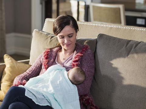 A mid adult woman in her 30s, holding her beautiful 2 month old baby girl, sitting on a sofa at home, nursing.