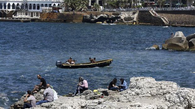 Residents of the Lebanese capital Beirut gather on the rocks along the seaside corniche, despite the lingering threat of the novel coronavirus, on May 31, 2020. (Photo by ANWAR AMRO / AFP)