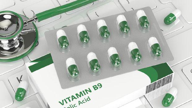 3d render of B9 folic acid pill  lying on keyboard in office
