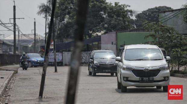 Sejumlah kendaraan melintas dekat tiang listrik yang berada di tengah jalan di kawasan Pasar Minggu, Jakarta, Jumat, 7 Agustus 2020. Tiang listrik tersebut terdampak pembangunan pelebaran jalan yang dilakukan di kawasan itu, namun, keberadaan tiang listrik yang tidak pada jalurnya ini dapat membahayakan pengendara yang sedang melintas di jalan tersebut. CNN Indonesia/Bisma Septalisma