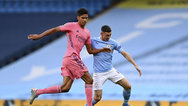 Real Madrid's Raphael Varane, left, is challenged by Manchester City's Phil Foden during the Champions League round of 16, second leg soccer match between Manchester City and Real Madrid at the Etihad Stadium stadium in Manchester, England, Friday, Aug. 7, 2020. (Shaun Botterill, Pool via AP)