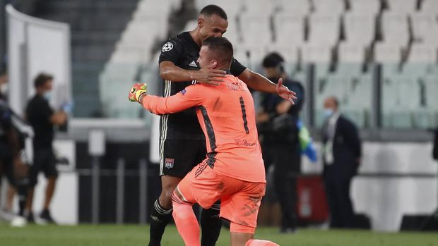 Lyon's goalkeeper Anthony Lopes, right, celebrates after the Champions League round of 16 second leg, soccer match between Juventus and Lyon at the Allianz stadium in Turin, Italy, Friday, Aug. 7, 2020. Lyon will play in the quarter finals. (AP Photo/Antonio Calanni)