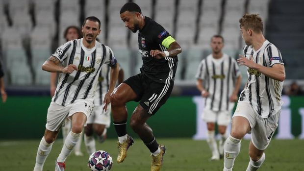Lyon's Memphis Depay, center, controls the ball during the Champions League round of 16 second leg, soccer match between Juventus and Lyon at the Allianz stadium in Turin, Italy, Friday, Aug. 7, 2020. (AP Photo/Antonio Calanni)