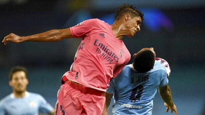 Real Madrids Raphael Varane jumps for a header with Manchester Citys Gabriel Jesus during the Champions League, round of 16, second leg soccer match between Manchester City and Real Madrid at the Etihad Stadium in Manchester, England, Friday, Aug. 7, 2020. (Oli Scarff/Pool Photo via AP)