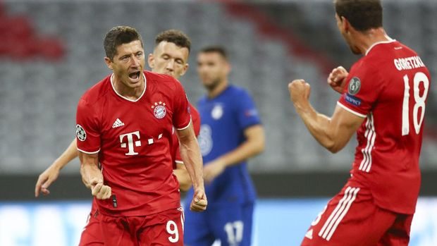Bayern's Robert Lewandowski, left, celebrates after scoring his team's first goal from the penalty spot during the Champions League round of 16 second leg soccer match between Bayern Munich and Chelsea at Allianz Arena in Munich, Germany, Saturday, Aug. 8, 2020. (AP Photo/Matthias Schrader)