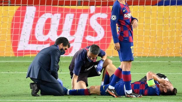 Barcelona's Argentine forward Lionel Messi reacts on the football pitch after being injured during the UEFA Champions League round of 16 second leg football match between FC Barcelona and Napoli at the Camp Nou stadium in Barcelona on August 8, 2020. (Photo by LLUIS GENE / AFP)