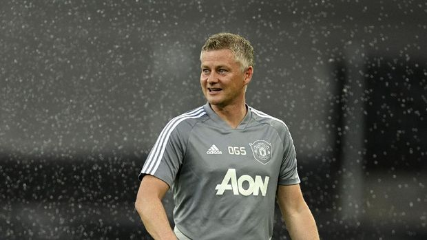 Manchester United's manager Ole Gunnar Solskjaer stands in the rain during a training session in Cologne, Germany Sunday Aug. 9, 2020. Copenhagen will play Manchester United in a Europa League quarterfinal soccer match on Monday. (AP Photo/Sascha Steinbach, Pool)