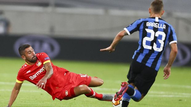 Leverkusen's Kerem Demirbay, left, kicks at the ball as Inter Milan's Nicolo Barella watches during the Europa League quarterfinal match between Inter Milan and Bayer Leverkusen at the Duesseldorf Arena in Dusseldorf, Germany, Monday, Aug. 10, 2020. (Dean Mouhtaropoulos, Pool Photo via AP)