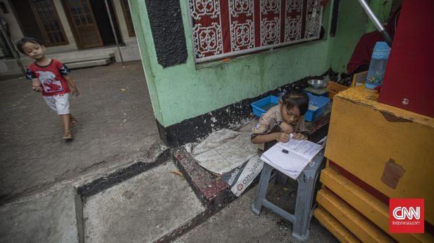 Siswi kelas 2 SDN 01 Pagi Bukit Duri ,Keysha (8) menjalankan proses belajar daring bersama ibunya, Okta (31) di gerai makanan tempat ibunya bekerja di kawasan Bukit Duri, Jakarta, Rabu, 12 Agustus 2020. Pembelajaran Jarak Jauh (PJJ) dengan menggunakan metode daring dan bimbingan orang tua masih menjadi kendala, menurut Okta selain harus mencari nafkah untuk keluarganya Ia harus tetap membimbing anaknya belajar di tempatnya bekerja. CNN Indonesia/Bisma Septalisma